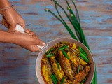 Piajkoli ar Aloo diye Tangra Macher Jhol (Bengali Light fish curry prepared with Tyangra Maach, Onion Stalks and Potato)