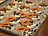Pretzels dipped in white chocolate & topped with crushed oreos